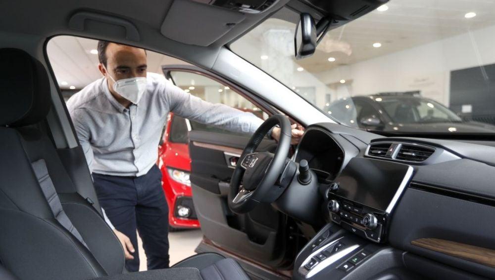 Un hombre con mascarilla observa un coche