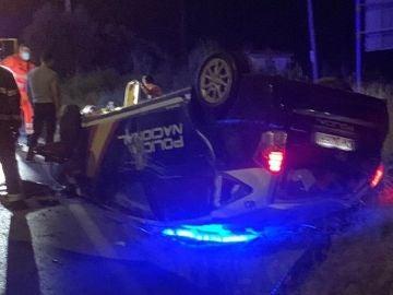 Imagen del coche patrulla volcado tras ser embestido por un narco