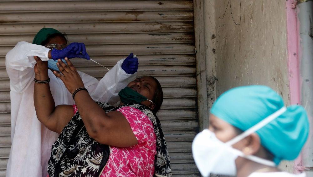 Un sanitario intenta hacer una PCR a una paciente en Mumbai