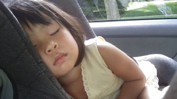 Niña dormida en el coche