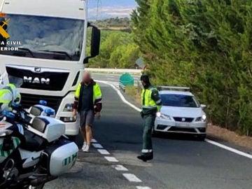 El camionero junto a un agente de la Guardia Civil