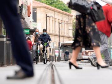 Dos personas circulan en bicicleta por una calle de Vitoria.