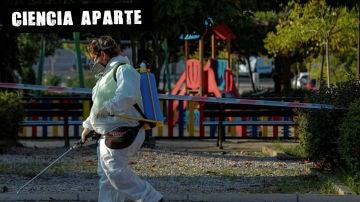 Una trabajadora municipal desinfecta las proximidades un parque infantil clausurado en la localidad madrileña de Alcobendas, Madrid