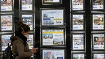 Una mujer pasa por delante de un portal inmobiliario de venta y alquiler