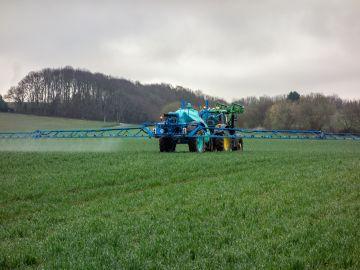 Un tractor realiza trabajos de fumigación en el campo.