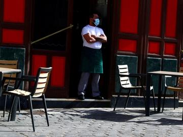 Un camarero con mascarilla espera a clientes en una terraza de Madrid