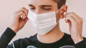 Un joven con mascarilla usa auriculares