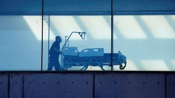 Un celador transporta una camilla en un hospital
