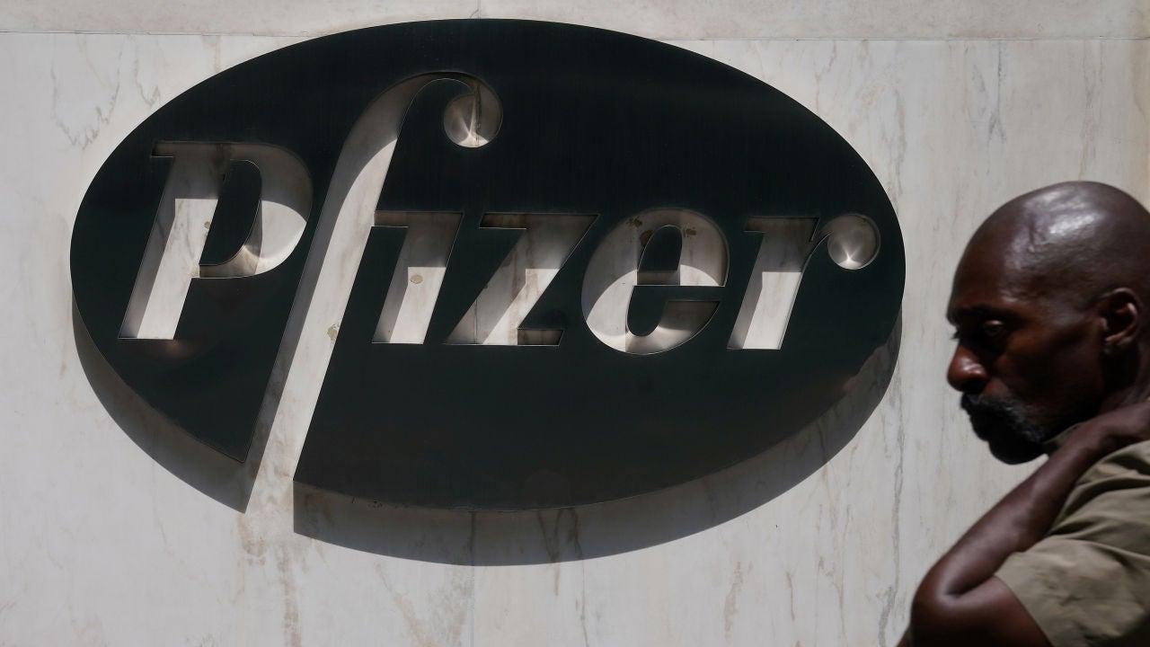 Un hombre camina frente a la sede de Pfizer