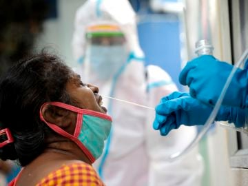 Un sanitario recoge una muestra durante una prueba rápida de COVID-19 en un centro de pruebas de Kolkata, India