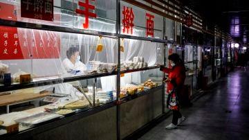 Una mujer compra en un mercado de Pekín