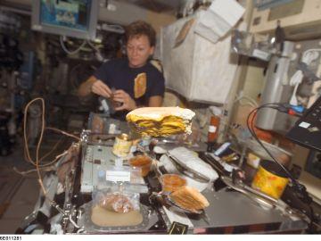 Astronauta preparando una comida.