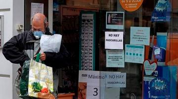 Un hombre sale de una farmacia en L´Hospitalet (Barcelona)