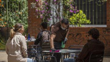 Un hostelero atiende una terraza en Sevilla