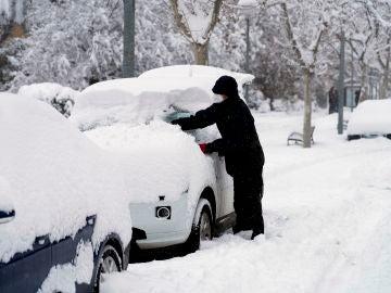 Hombre limpiando nieve de su coche
