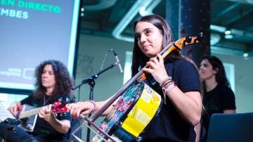 Una joven de la orquesta de 'La música del reciclaje' toca un instrumento construido con residuos