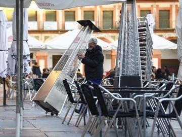 Un trabajador recoge el mobiliario de la terraza de un restaurante en el centro de Córdoba