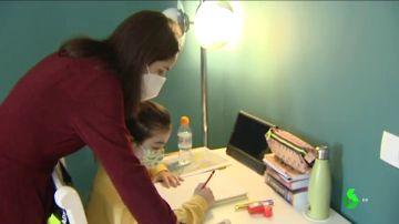 Imagen de una niña con patologías previas haciendo los deberes con su madre
