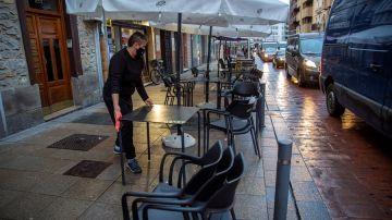 Un camarero monta la terraza de su bar en Vitoria después de que se levante su cierre.