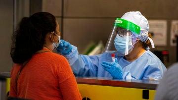 Una profesional sanitaria realiza una prueba PCR a una paciente