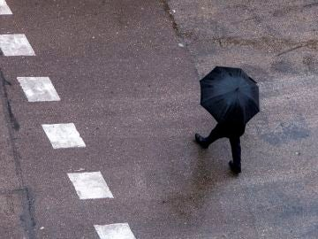 Un hombre pasea con un paraguas