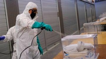 Un operario desinfecta una urna de votación en Cataluña