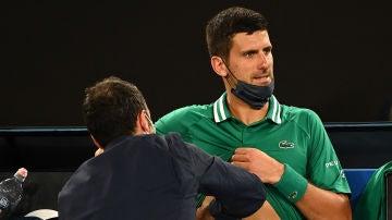 Un médico atiende a Novak Djokovic durante el Open de Australia