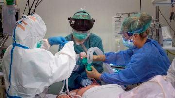 Una doctora y dos enfermeras atienden a un paciente de coronavirus