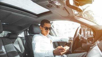 Un hombre hace uso de su teléfono móvil mientras conduce