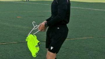 Árbitro asistente con una percha y un peto, en el partido entre Ciudad de Murcia y Villareal.