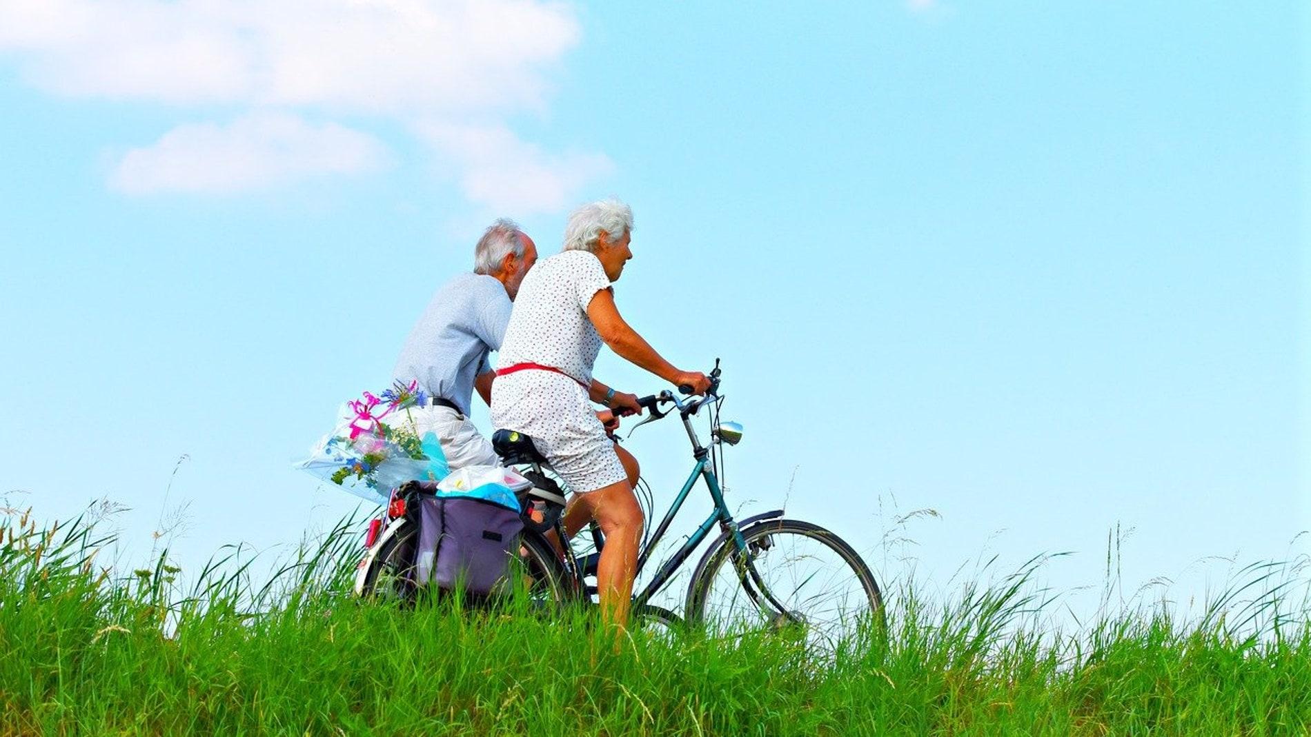 hombre y mujer mayores de 65 años en bicicleta