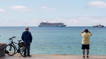 Unos hombres observan un crucero turístico en la bahía de Palma de Mallorca
