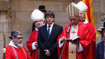 Puigdemont, escuchando al cardenal de Barcelona, Juan José Omella, en una imagen de archivo.