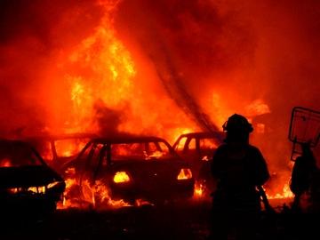 Un bombero intenta apagar un incendio de un estacionamiento del tránsito tras una nueva jornada de protesta en Colombia.