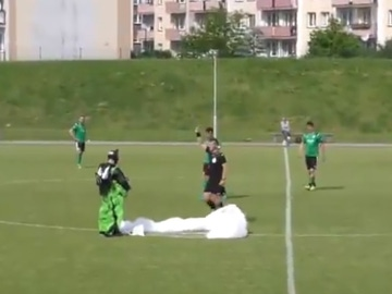 Un paracaidista aterriza en pleno partido de fútbol... y el árbitro le saca tarjeta amarilla