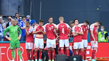 Jugadores de la selección danesa se colocan alrededor de Eriksen mientras está siendo atendido