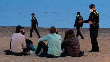 Un grupo de personas sentado en una playa de Barcelona