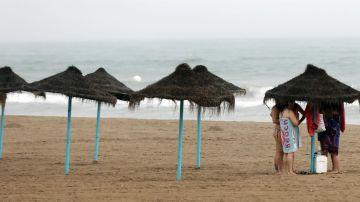 Unos bañistas se protegen de la lluvia bajo una sombrilla