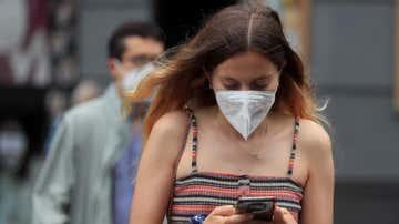 Una joven con mascarilla camina por Madrid