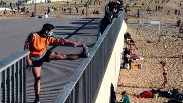 Varias personas, con la mascarilla puesta, practican deporte en la playa