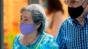 Varias personas con mascarilla caminan por una calle de Madrid