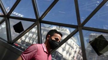 Un hombre con una mascarilla camina por la estación de Sol de Madrid