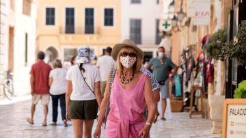 Una mujer caminando con mascarilla por la calle