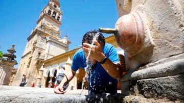 Un hombre se refresca en una fuente céntrica de Córdoba debido a las altas temperaturas registradas.