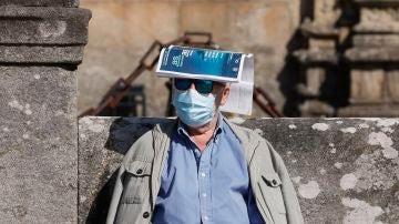 Un hombre se protege del sol con una revista sobre la cabeza en la plaza del Orbadoiro en Santiago de Compostela.