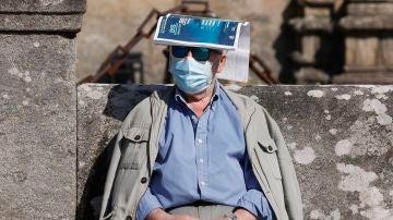 Un hombre se protege del sol con una revista sobre la cabeza en la plaza del Orbadoiro en Santiago de Compostela