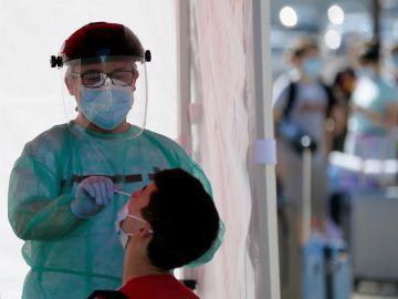 Un efectivo de Cruz Roja realiza una prueba PCR a un joven en Valladolid