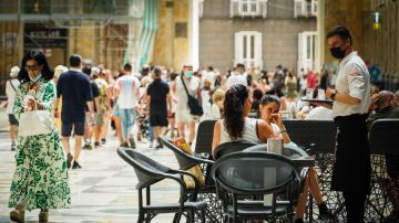 Un camarero atiende a los clientes en la terraza de un restaurante en Nápoles, Italia.