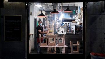 Un trabajador recoge el interior de una cafetería de Madrid