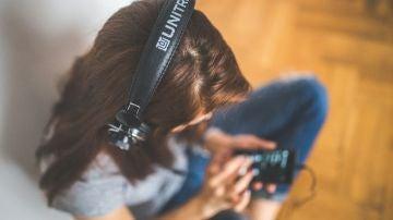 Una persona escucha música con cascos (Archivo)